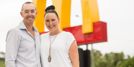 Man and Woman Smiling In Front of McDonald's Signage