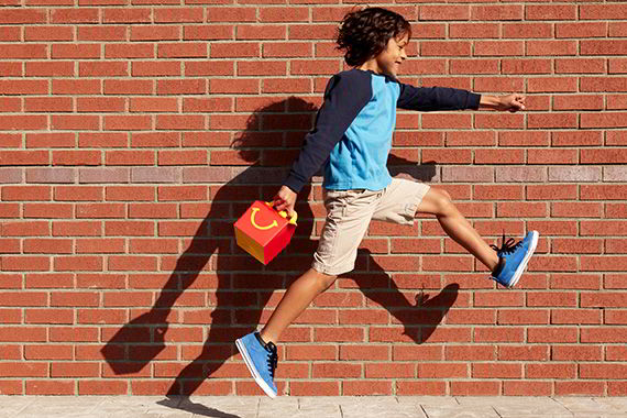 A boy jumping in the air holding a McDonald's Happy Meal