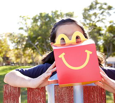 A child holding the McDonald's Happy Meal container in front of their face