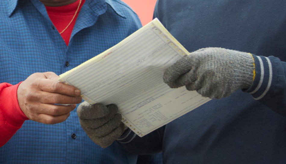 Two people holding up a piece of paperwork
