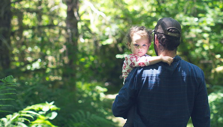 A daughter and her father walking through a forest