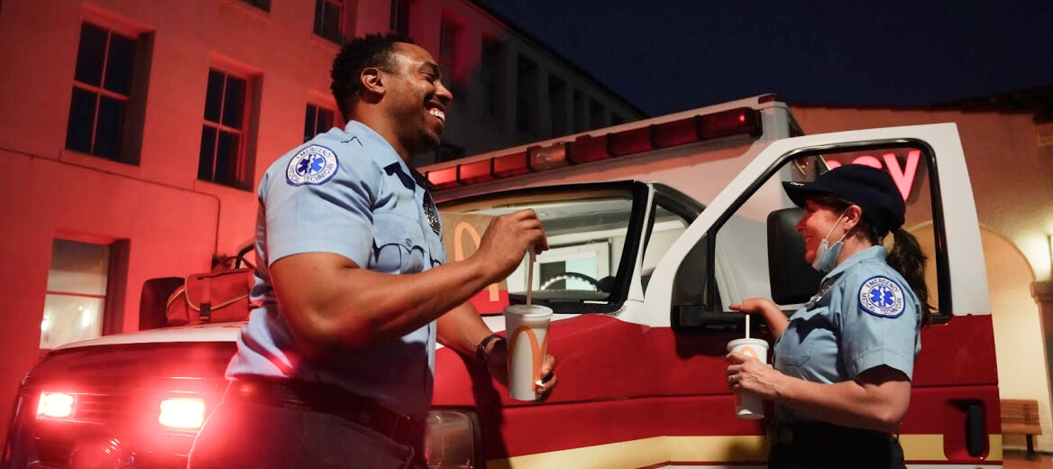 two paramedics standing next to an ambulance smiling and eating McDonald's food and drinks