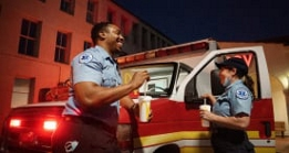Two Emergency Medical Technicians eating McDonald's outside of an ambulance