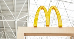McDonald's Golden Arches on top of a wooden frame outside of a restaurant