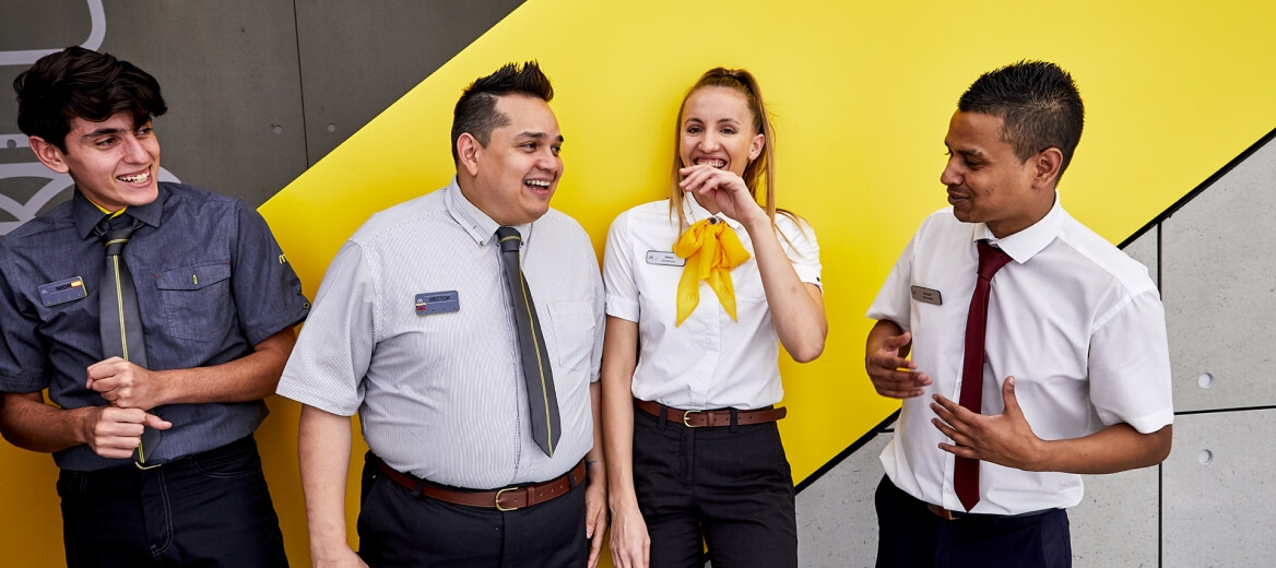 four McDonald's employees standing together outside of a restaurant smiling and laughing