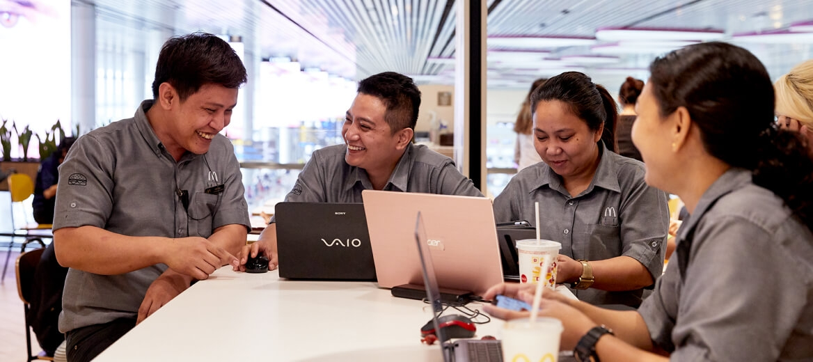 a McDonald's employees smiling around a table with laptop computers