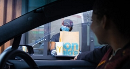 Masked McDonald's employee handing customer order through takeout window