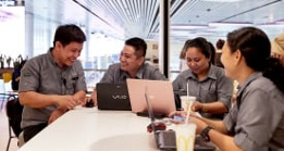 Four McDonald's employees working together at a table with laptops