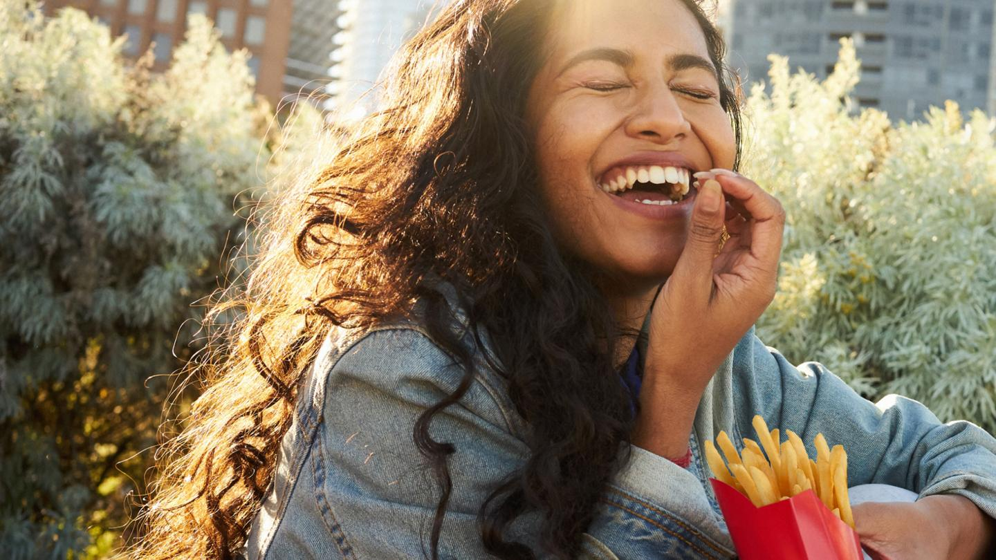 woman enjoying fries at mcdonalds